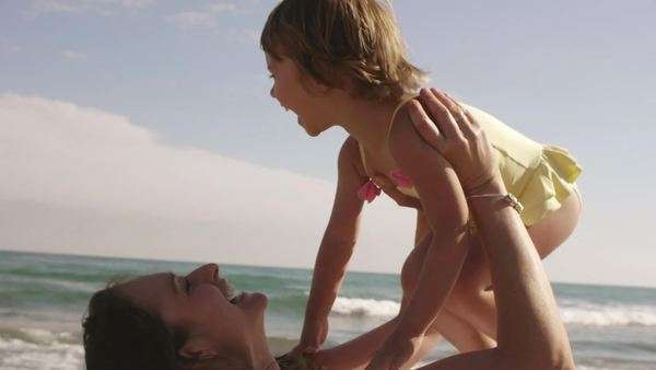 Mother and daughter playing and hugging at the beach. Royalty-free stock video