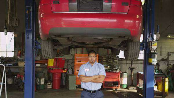 Portrait of auto mechanic standing in shop Royalty-free stock video