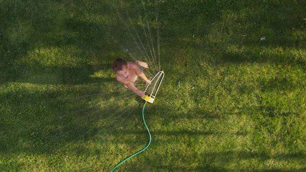 Child playing in sprinkler, overhead shot Royalty-free stock video