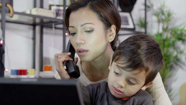 A busy mother is working from home on her computer, talking on the telephone and taking care of her son, all at the same time Royalty-free stock video