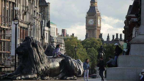A stationary shot of people climbing on a giant lion at the foot of Lord Nelson's monument on Trafalgar Square in London. Buildings and Big Ben can be seen in distance. Filmed on October 7, 2011. Royalty-free stock video