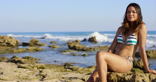 317ea2db82 Sexy tanned happy young woman sitting on rocks at the seaside in a bikini  smiling happily at the camera on a rocky shoreline stock footage