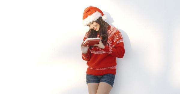 a629c6c4e74 Cute brunette woman in Santa Claus hat she standing isolated against white  background she wearing red Christmas woolen sweater - slow motion