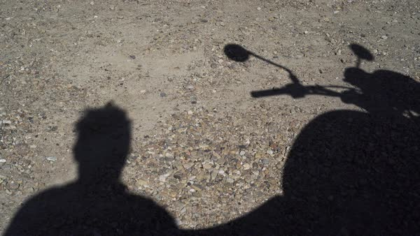 Medium shot of shadow of a man and his motorcycle Royalty-free stock video
