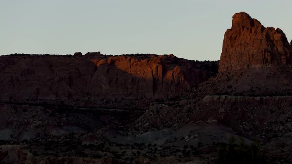 The sun's light rolls over hills and cliffs at sunset near Capitol Reef, Utah. Long-lens shot. Royalty-free stock video