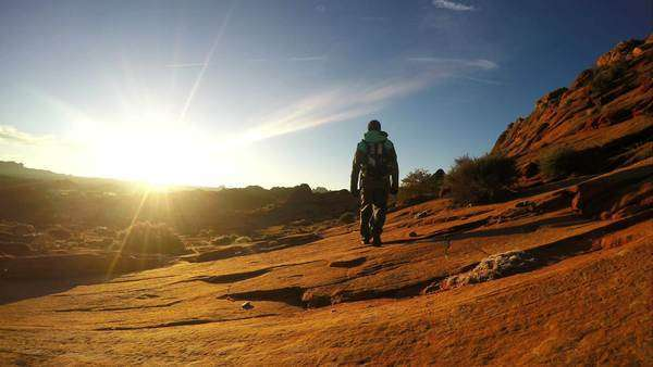 Man hiking over sandstone toward the sun in slow motion. Royalty-free stock video