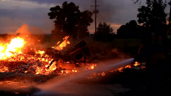 View of fireman spraying hose on fire where house burned down at dusk. Royalty-free stock video