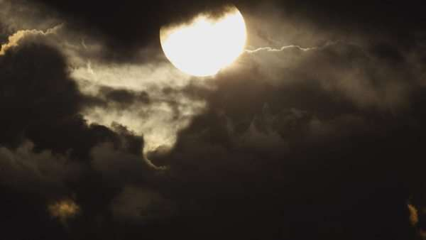 Epic sun movement close-up through dark storm ominous clouds. Dramatic timelapse aerial shot of sun disc movement behind rolling ominous dark clouds. No flickering or exposure changes, and all unwanted elements such as birds/planes etc. have been digitally removed. Royalty-free stock video