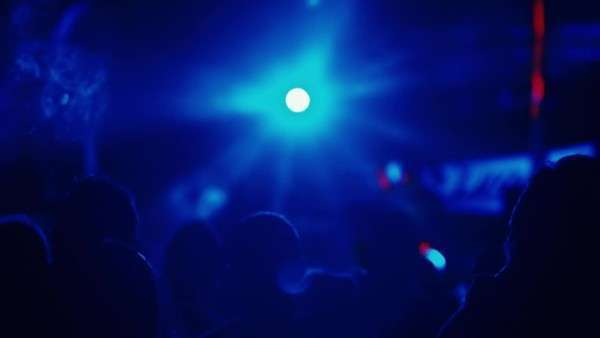 People at a party backlit and silhouetted by strobing colorful stage lights. Royalty-free stock video