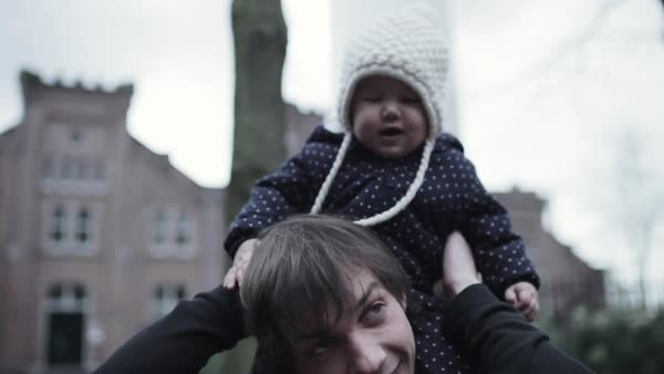 Medium shot of a father carrying his baby on his shoulders Royalty-free stock video
