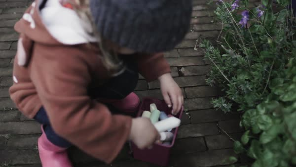 Medium shot of a little girl bringing out her chalks in a box Royalty-free stock video