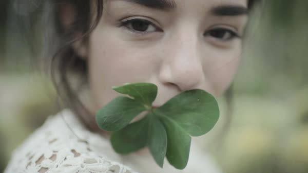 Close-up shot of a woman holding a leaf in her mouth Royalty-free stock video