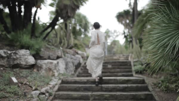 Wide shot of a woman walking up on stairs in an open back dress Royalty-free stock video