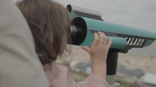 Hand-held shot of a girl looking through an outdoor telescope in arms of her father Royalty-free stock video