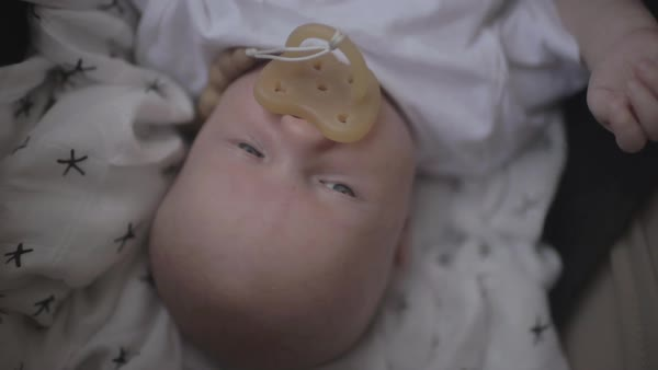Hand-held shot of a baby lying with a pacifier in mouth Royalty-free stock video