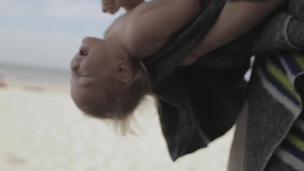 Hand-held shot of a young mother playing with her child on a beach Royalty-free stock video