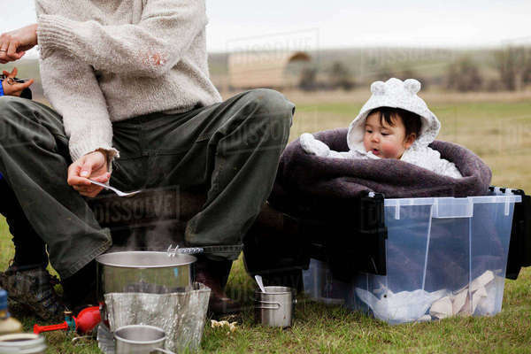 3bbfd4bc7 A 6 month old Japanese American baby girl sits in a plastic tub ...