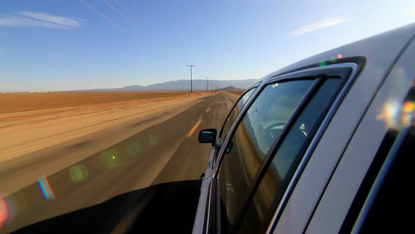 Camera attached on the side of the car driving on deserted highway  POV of  car driving on desert road  Car turning right  stock footage