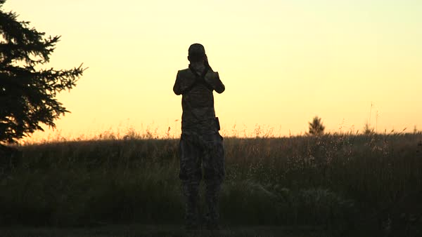 Wide shot of a hunter standing in a field at sunset Royalty-free stock video