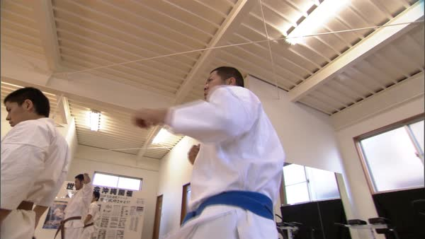 Hand-held shot of karate fighters doing warm-up in a dojo in Okinawa Rights-managed stock video