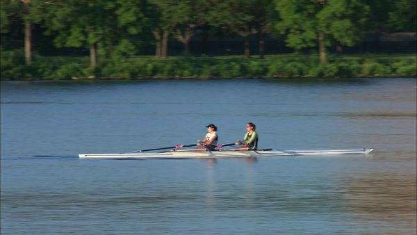 Tracking shot of two women rowing on Charles River in Boston Rights-managed stock video