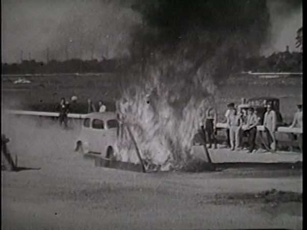 Vintage atuntman rides car hood through flames Rights-managed stock video