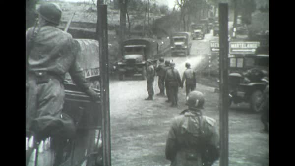 US trucks rolling in during WW2 with soldiers watching stock footage