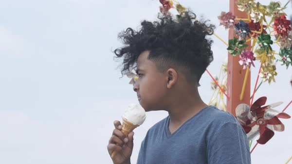 Dolly shot view of a young boy eating ice cream  Royalty-free stock video