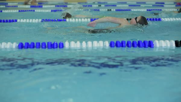 Side low angle view of children swimming in lanes in indoor pool during school sport training Royalty-free stock video