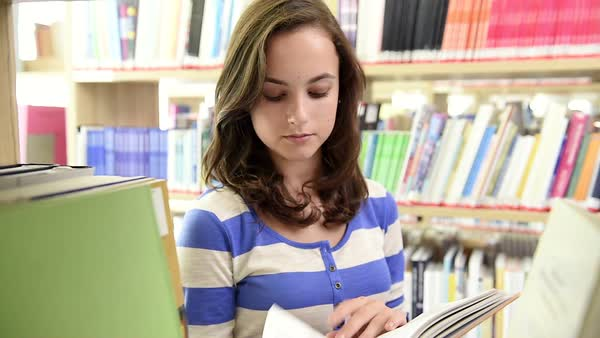 Dolly shot through bookshelf of happy female student in college library Royalty-free stock video