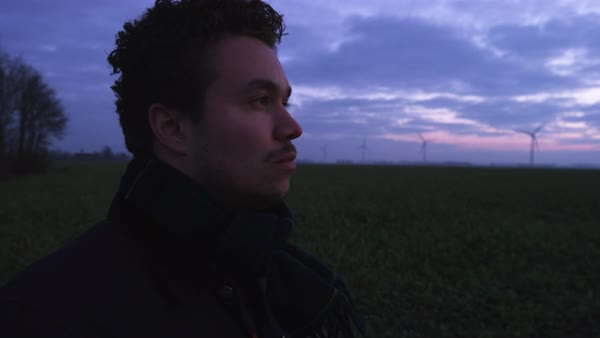 Hand-held shot of a man staring in a field at dawn Royalty-free stock video