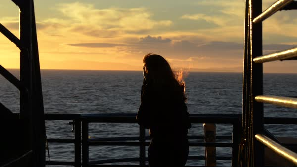 Hand-held shot of a woman watching sunset on a boat Royalty-free stock video