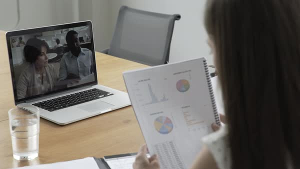 Hand-held shot of three people sitting at office desk during a video call conference Royalty-free stock video