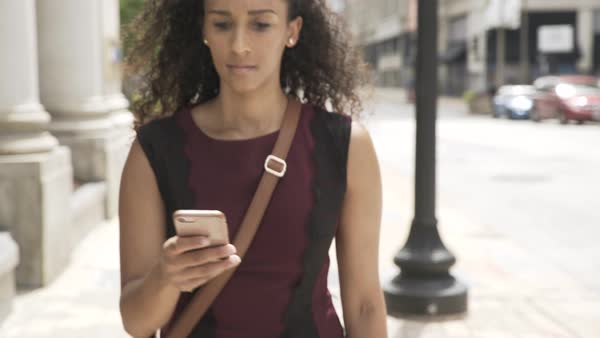 Tracking shot of a woman using her cell phone on a street Royalty-free stock video