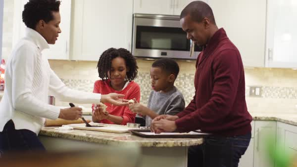 Family putting Christmas cookies onto baking pan Royalty-free stock video