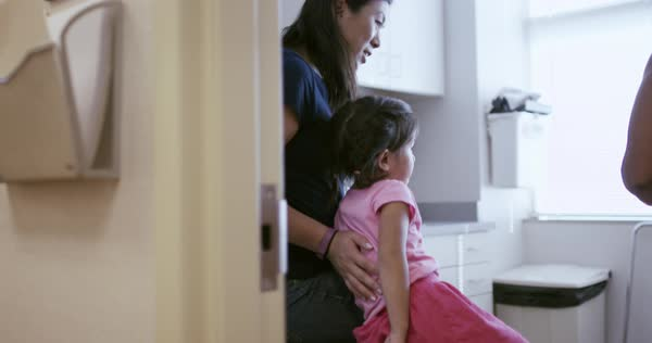 Pediatrician talking to mother and daughter in examination room Royalty-free stock video