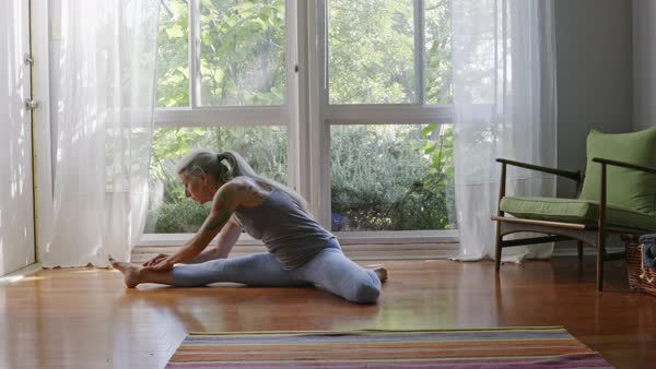 Mature Caucasian Woman Practicing Yoga On Livingroom Floor   Stock Video  Footage   Dissolve