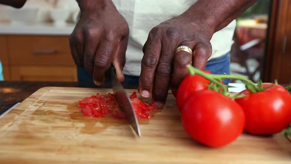 Hands of African American man chopping tomato on cutting board Royalty-free stock video