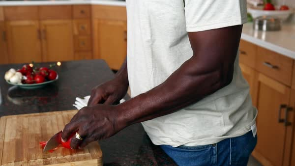 Smiling African American man chopping tomato in domestic kitchen Royalty-free stock video