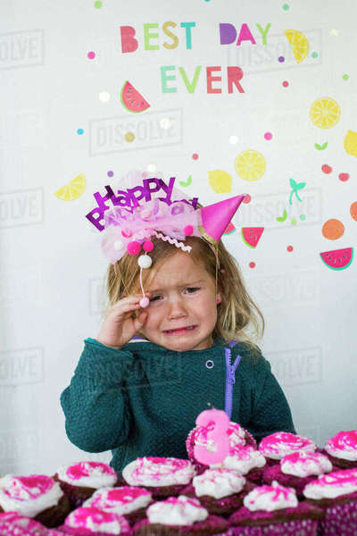 caucasian girl crying over tray of cupcakes for birthday