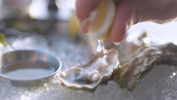 Close-up shot of lemon being added to raw oyster Rights-managed stock video