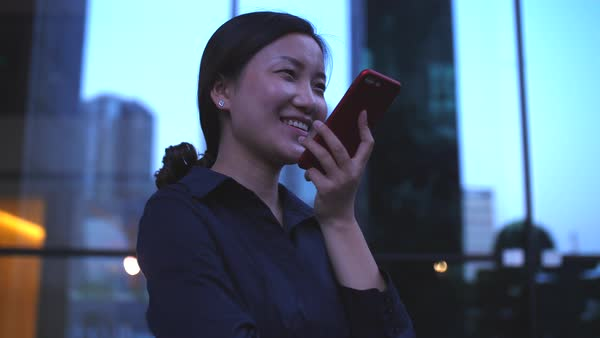 Happy Businesswoman Talking On The Phone By The Office Building Window At Evening In Slow Motion Stock Footage