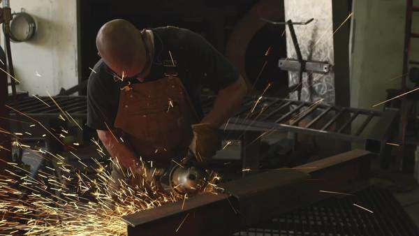 Handheld shot of man grinding metal in his workshop Royalty-free stock video