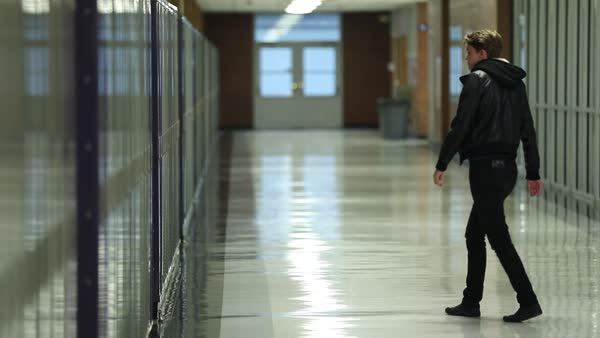 Teenager Walks Over To Lockers And Sits On The Ground Alone In