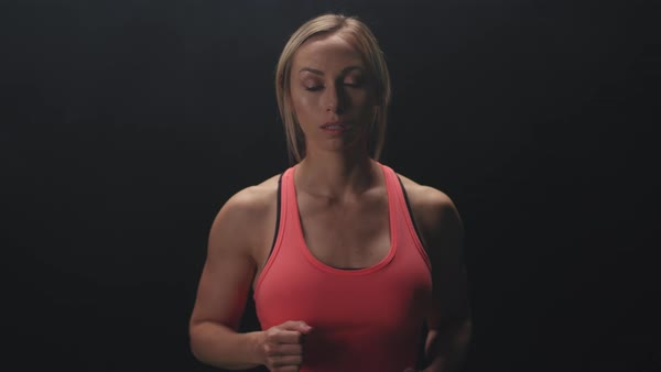 Athletic woman running in place, and then stands on a foggy dark background Royalty-free stock video