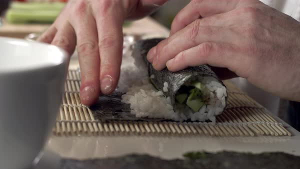 Sushi Chef Using Fingers To Wet Seaweed Paper For Fresh Sushi Roll