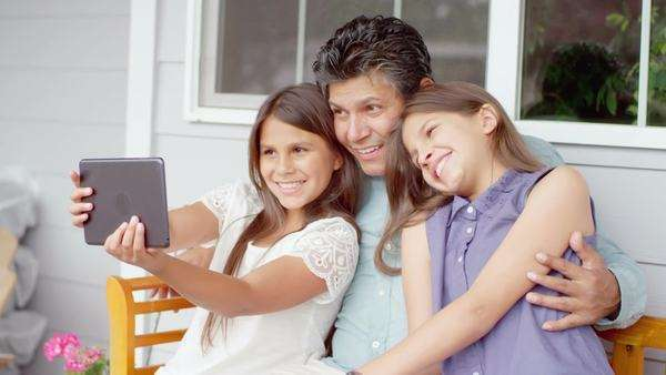 Slow motion shot of a father and his two daughters sitting on a bench and taking a selfie with a tablet Royalty-free stock video
