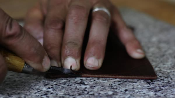 Close-up shot of a craftsman skiving a piece of leather Royalty-free stock video