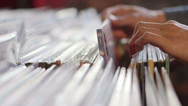 Close-up of A Young Man's fingers flick through a rack of vintage records Royalty-free stock video