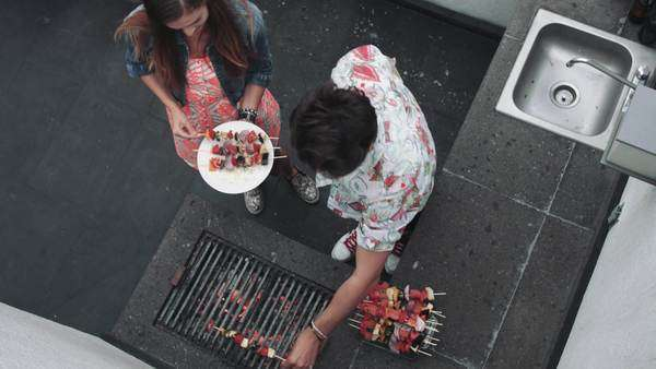 Man and woman having barbeque on rooftop terrace Royalty-free stock video